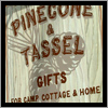 A hand painted background and vinyl lettering give the Pine Cone and Tassle sign a very unique look.