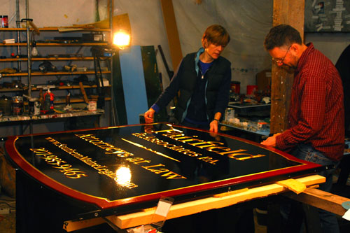 Kevin and Sandra Freeman are putting the finishing touches on a steel band around a large carved sign